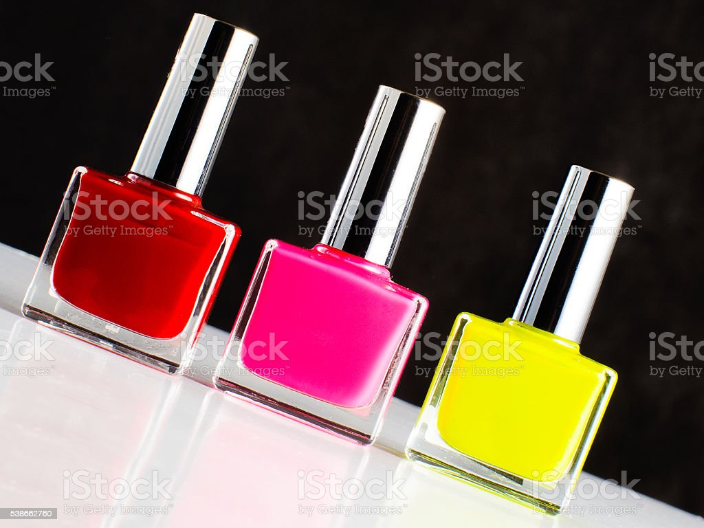 Three bottles of nail polish standing on sloping white surface stock photo