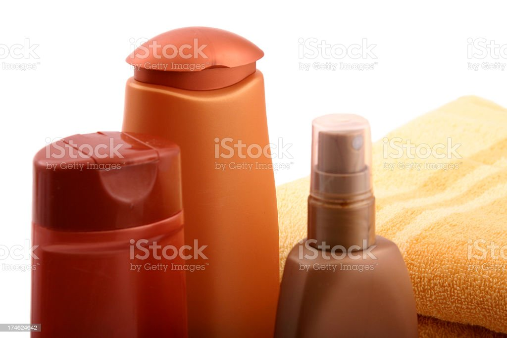 Three bottles of plastic cosmetics and a towel stock photo