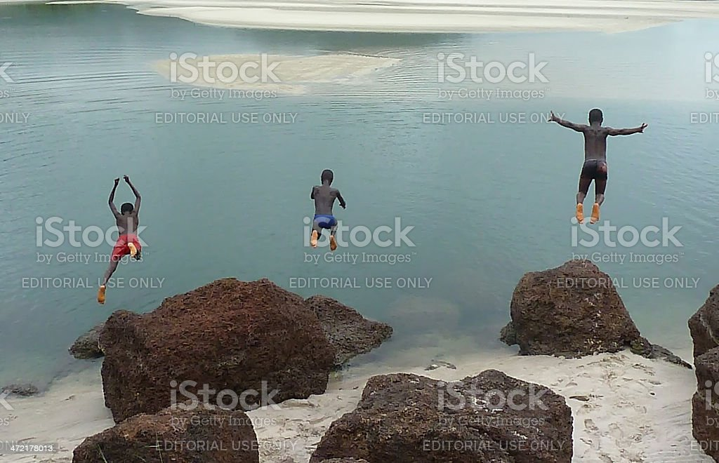 Three boys dive in a African lake stock photo