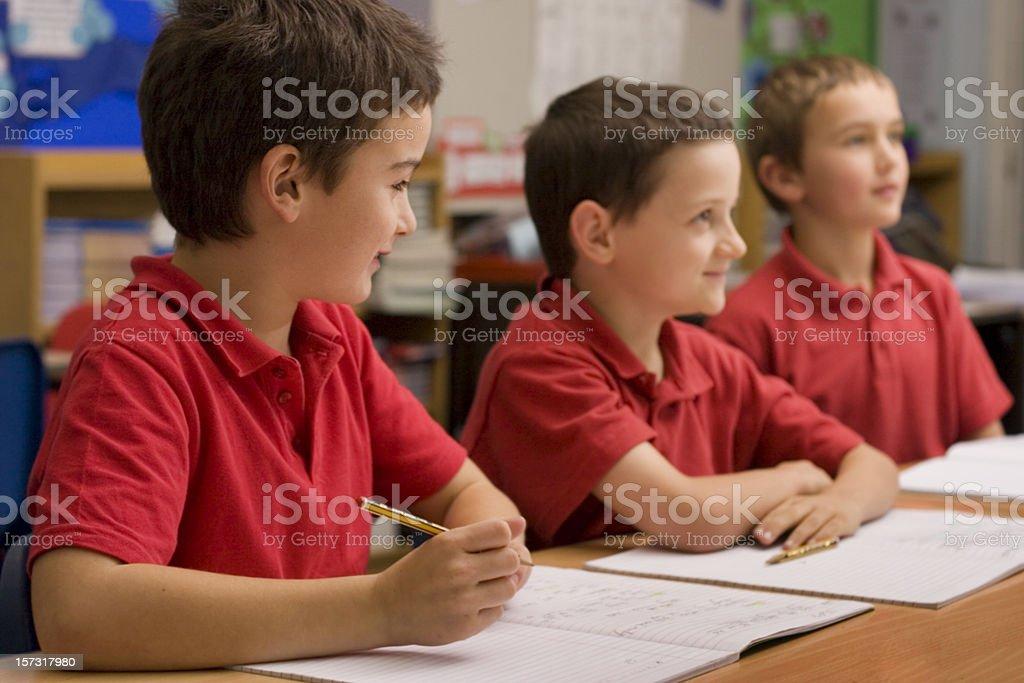 Three boys listening in classroom royalty-free stock photo