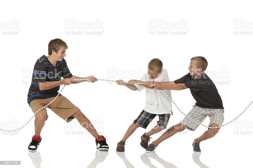 Three boys playing tug-of-war royalty-free stock photo