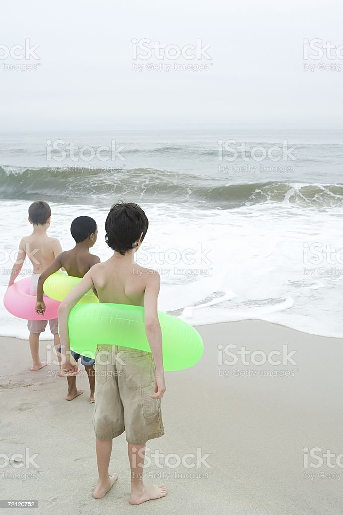 Three boys wearing inflatable rings royalty-free stock photo