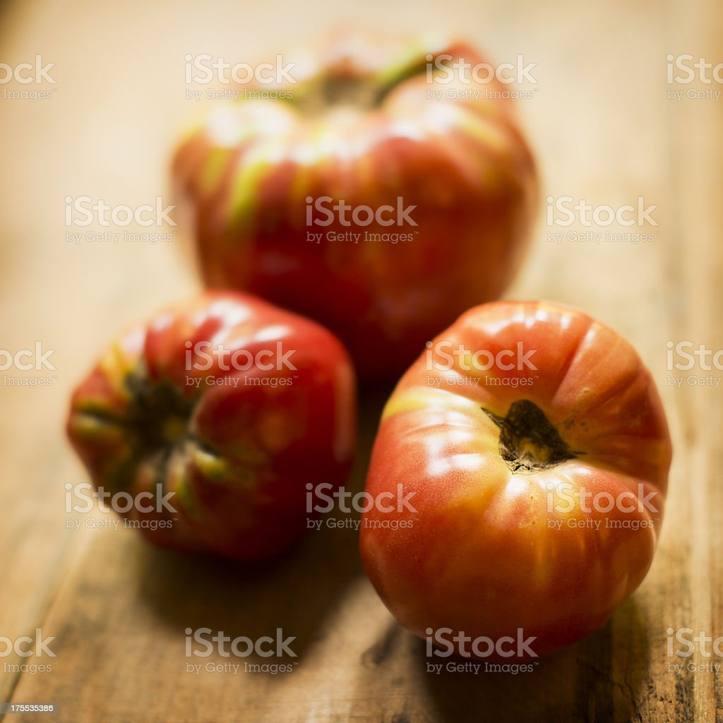 Three Brandywine Heirloom Tomatoes on a Wooden Crate royalty-free stock photo