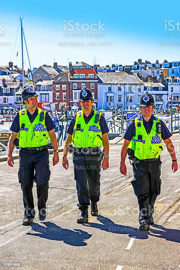 Three British Policemen walking around Weymouth, UK stock photo