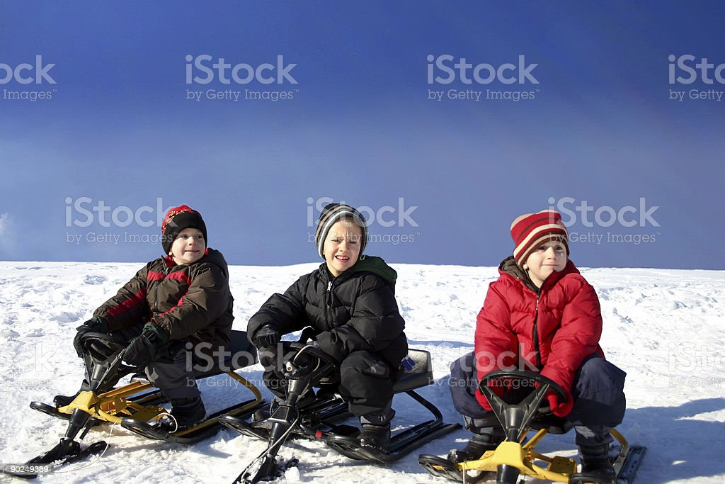Three brothers tobogganing stock photo