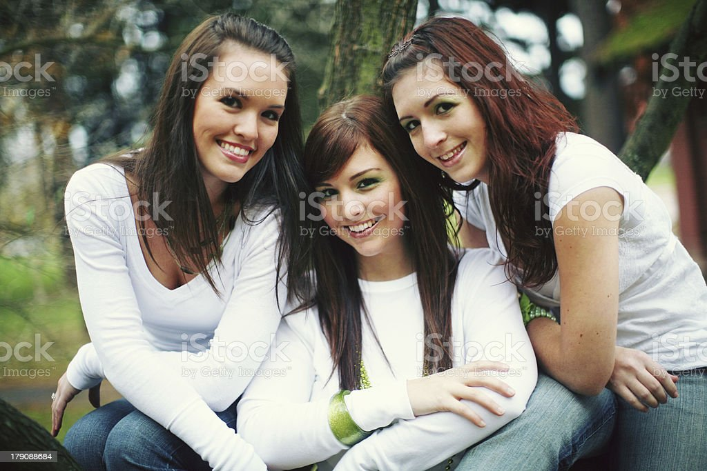 Three Brunette Girls with White and Jeans in a Park royalty-free stock photo