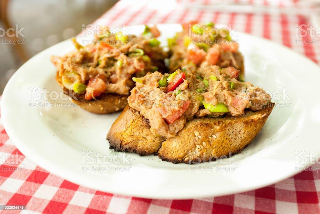 three bruschettas with tuna lying on plate at restaurant stock photo