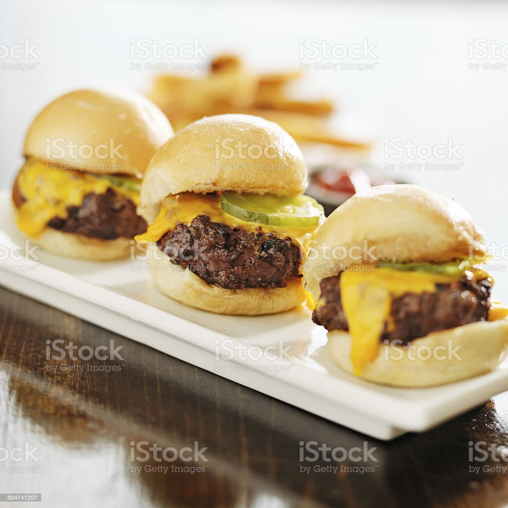 three burger sliders with cheese and pickle stock photo