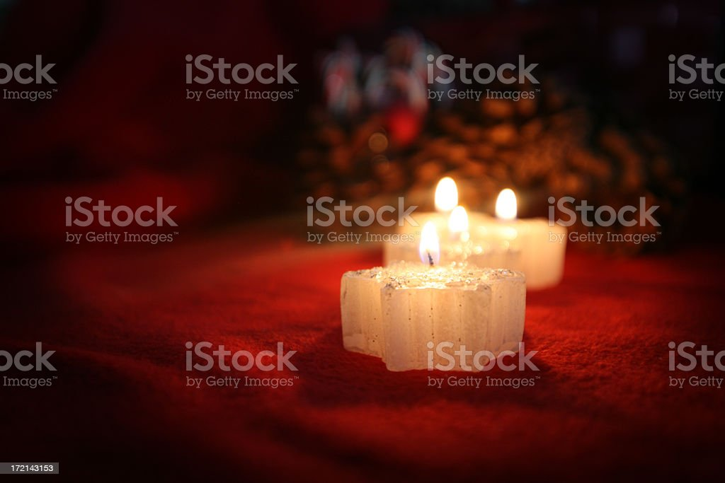 Three burning christmas candles on red mantle royalty-free stock photo