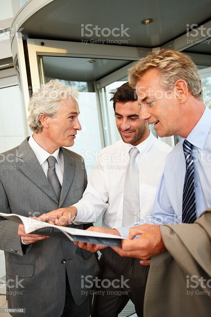 Three business colleagues discussing on document royalty-free stock photo