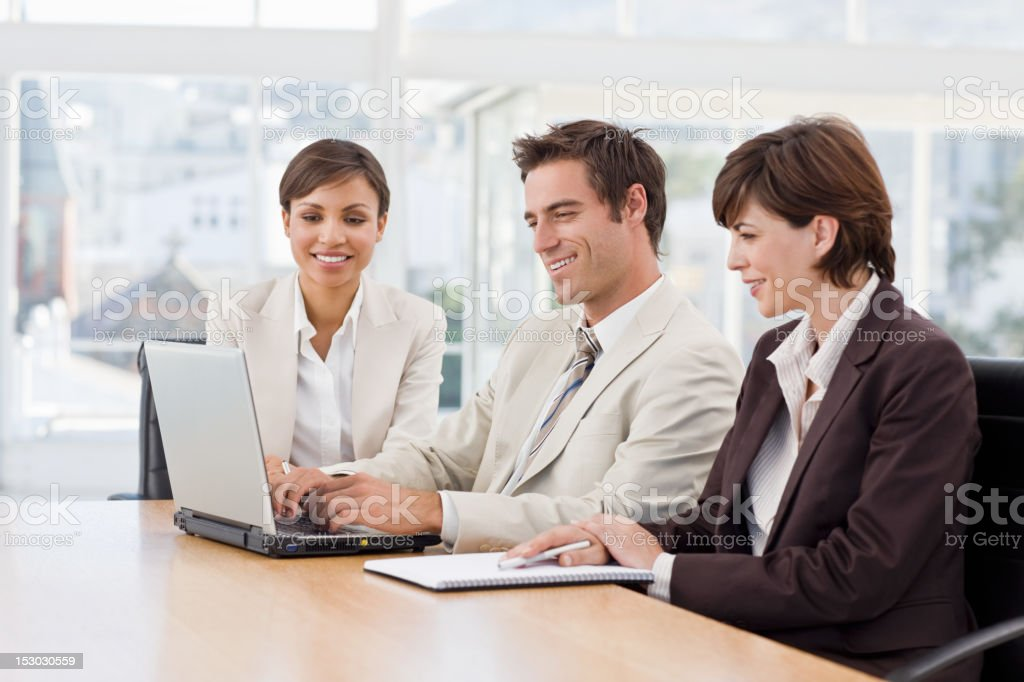 Three business colleagues working on laptop royalty-free stock photo
