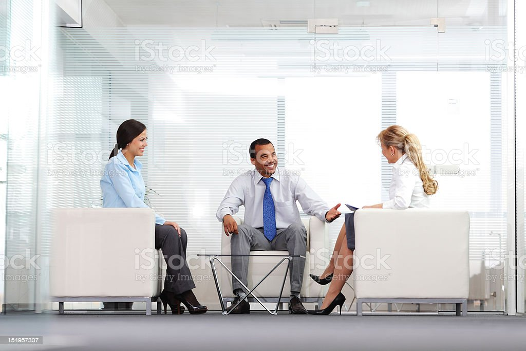 Three business co-workers have conversation at the workplace. royalty-free stock photo