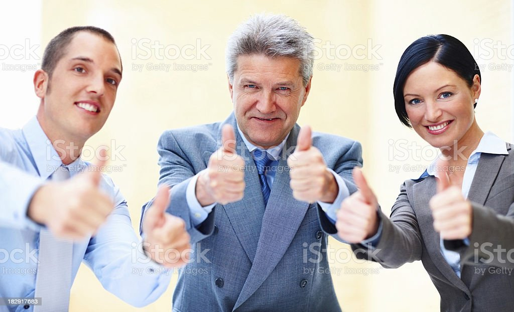 Three business partners holding their thumbs up royalty-free stock photo