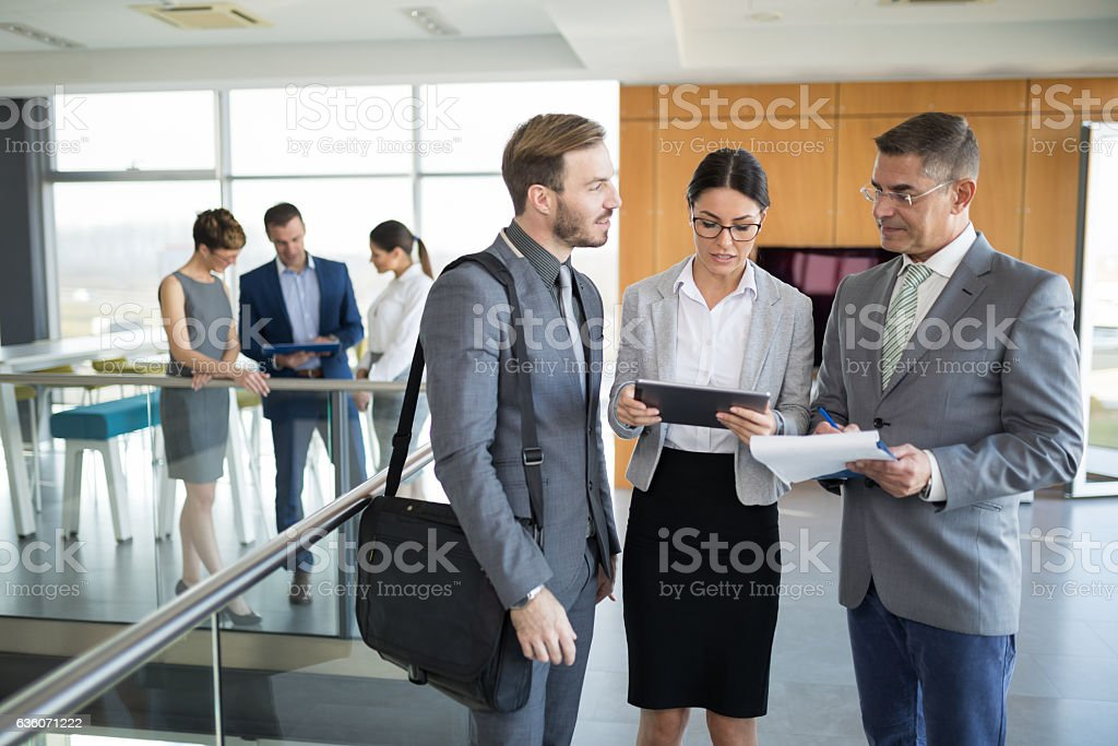 Three business people discussing business strategy using digital tablet stock photo