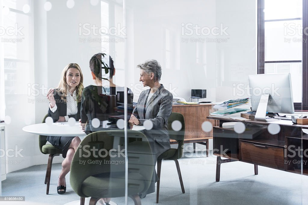 Three business people having meeting behind glass partition stock photo