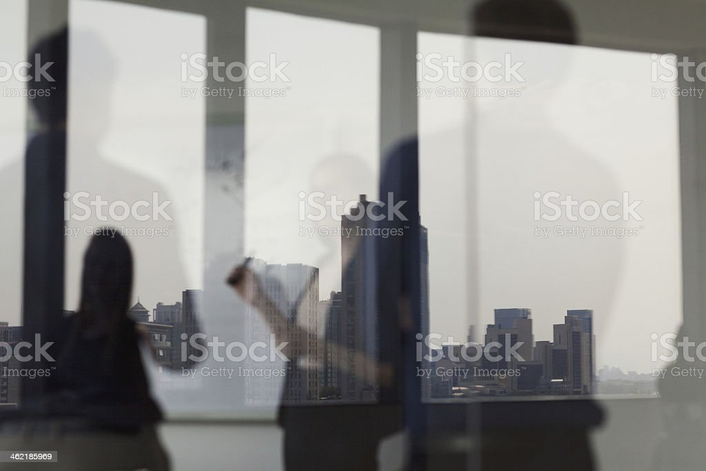 Three business people looking at a white board stock photo