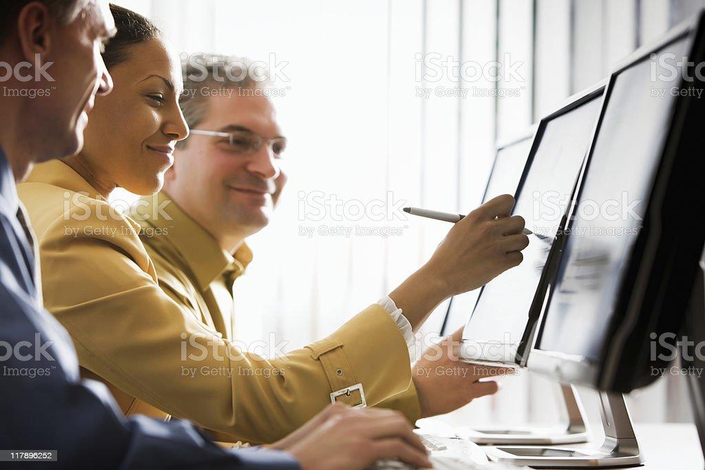 Three Business People Looking at Computer Monitors royalty-free stock photo