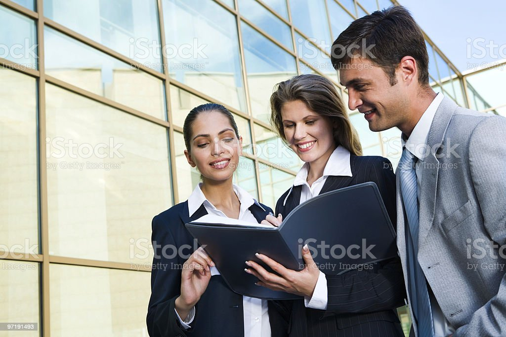 Three business people reviewing a business agreement stock photo