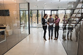 Three business people standing in a lobby and reading files.