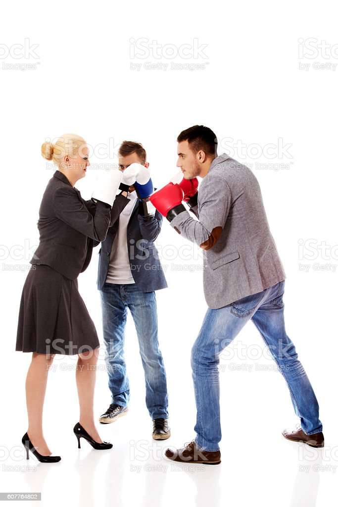 Three business people wearing boxing gloves start competition fight stock photo