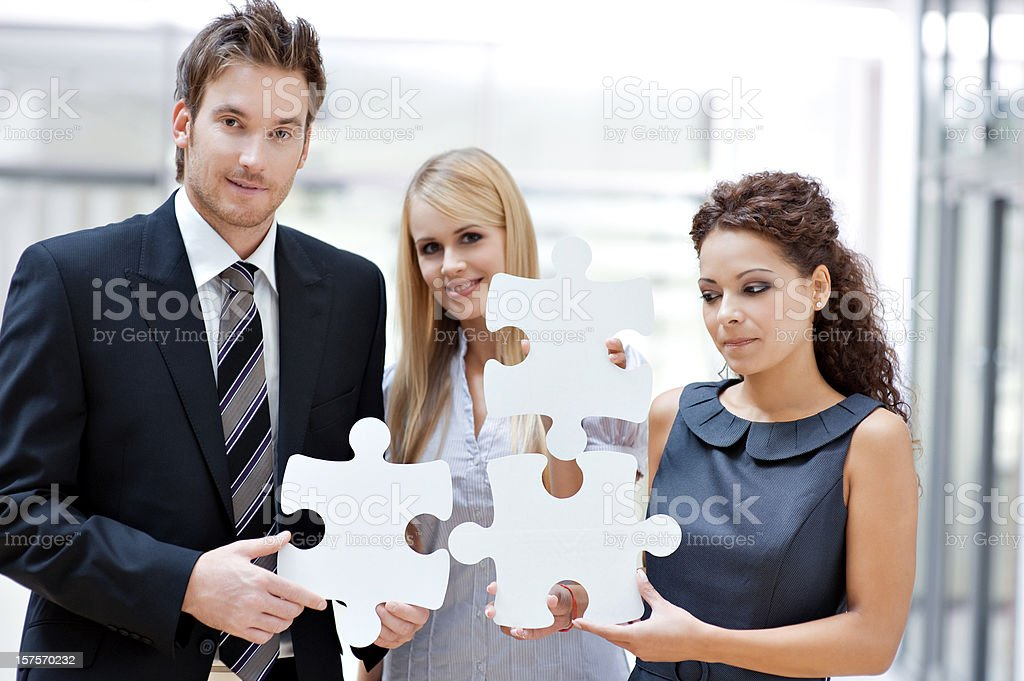 Three business people with puzzle royalty-free stock photo