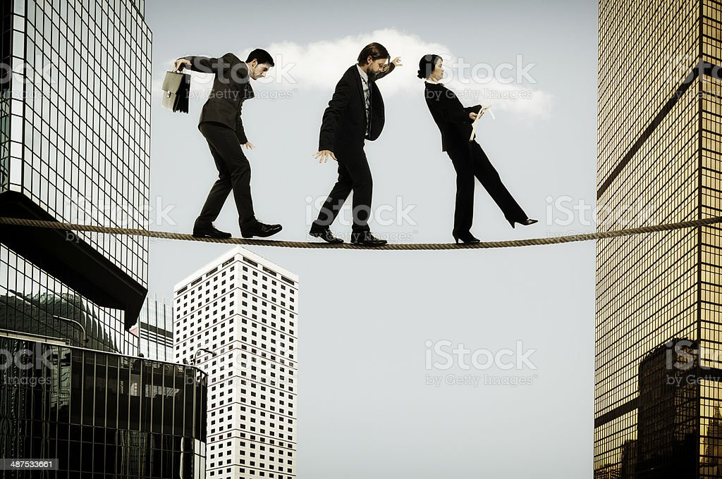 Three businessman tightrope walkers stock photo