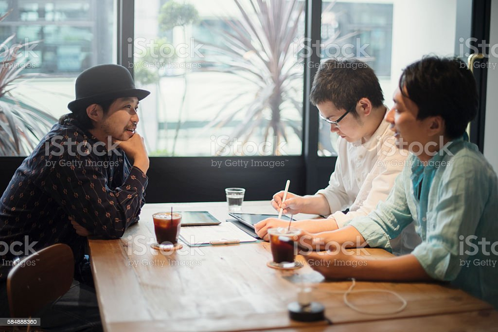Three Businessmen meeting in a cafe stock photo