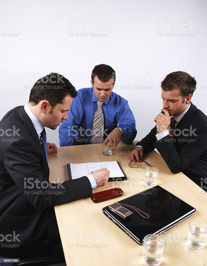 Three businessmen negotiating and signing a contract. royalty-free stock photo