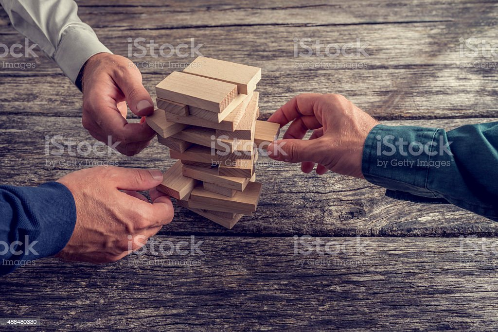 Three Businessmen Playing Wooden Tower Game stock photo