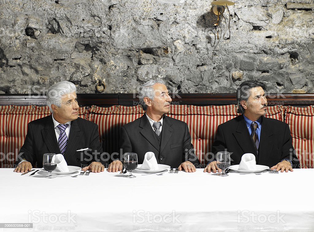 Three businessmen sitting in restaurant looking to side royalty-free stock photo