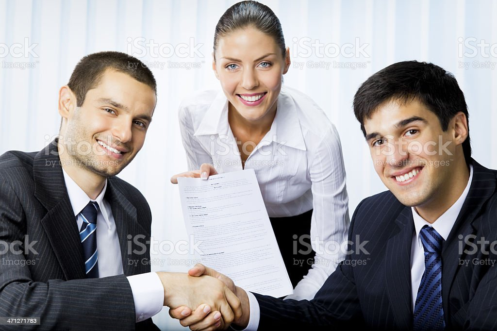 Three businesspeople handshaking with document at office royalty-free stock photo