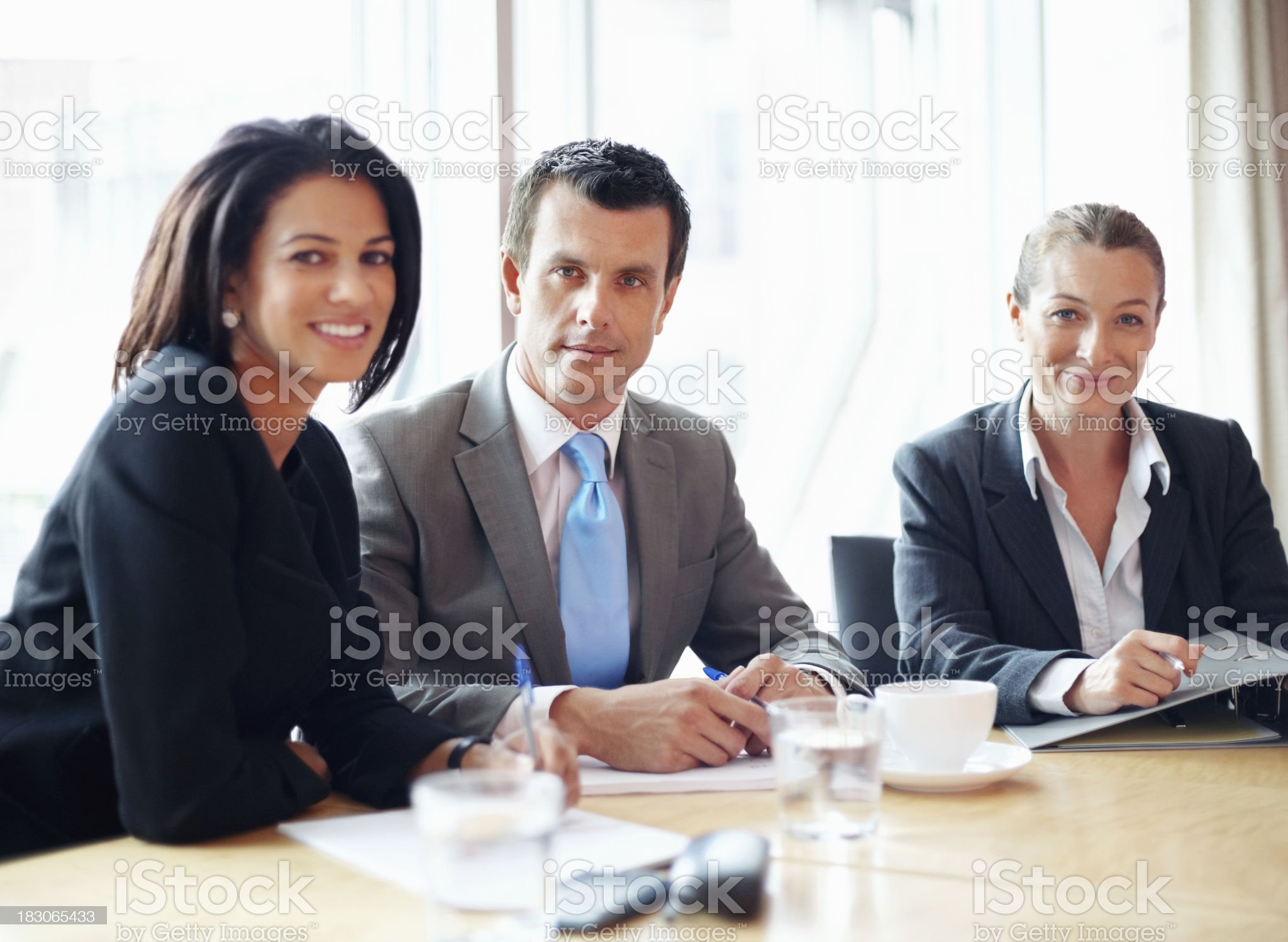 Three businesspeople having a meeting in conference room royalty-free stock photo