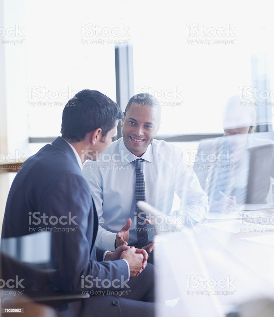 Three businesspeople in boardroom through glass stock photo