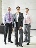 Three businesspeople in office smiling