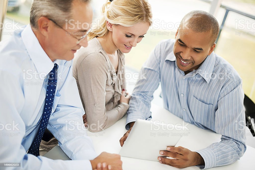 Three businesspeople looking on a touchpad. royalty-free stock photo