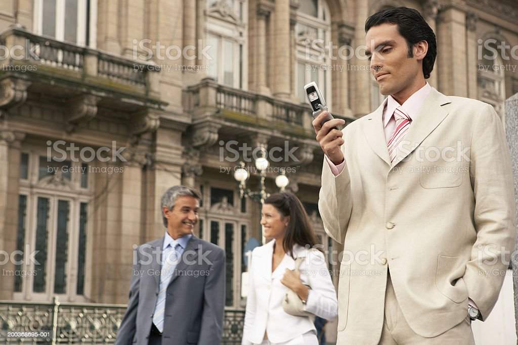 Three businesspeople, man using mobile phone, low angle royalty-free stock photo