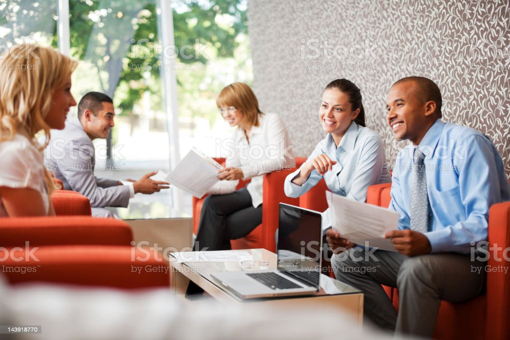 Three businesspeople sitting and holding files. royalty-free stock photo