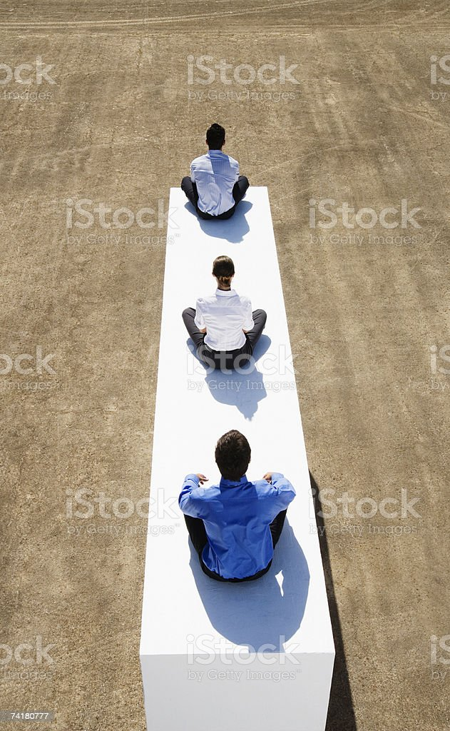 Three businesspeople sitting cross legged on wall outdoors royalty-free stock photo