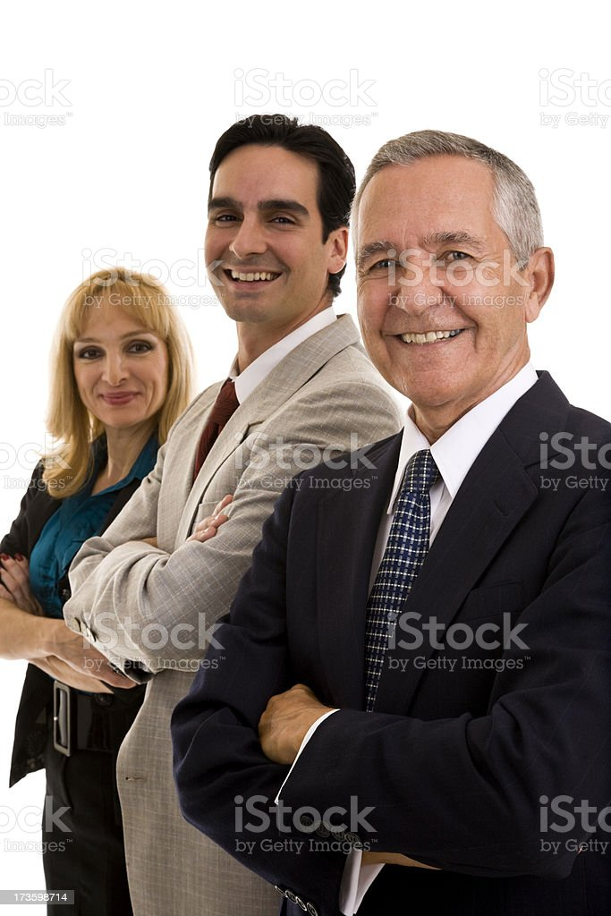 Three businesspeople standing in a row arms crossed royalty-free stock photo