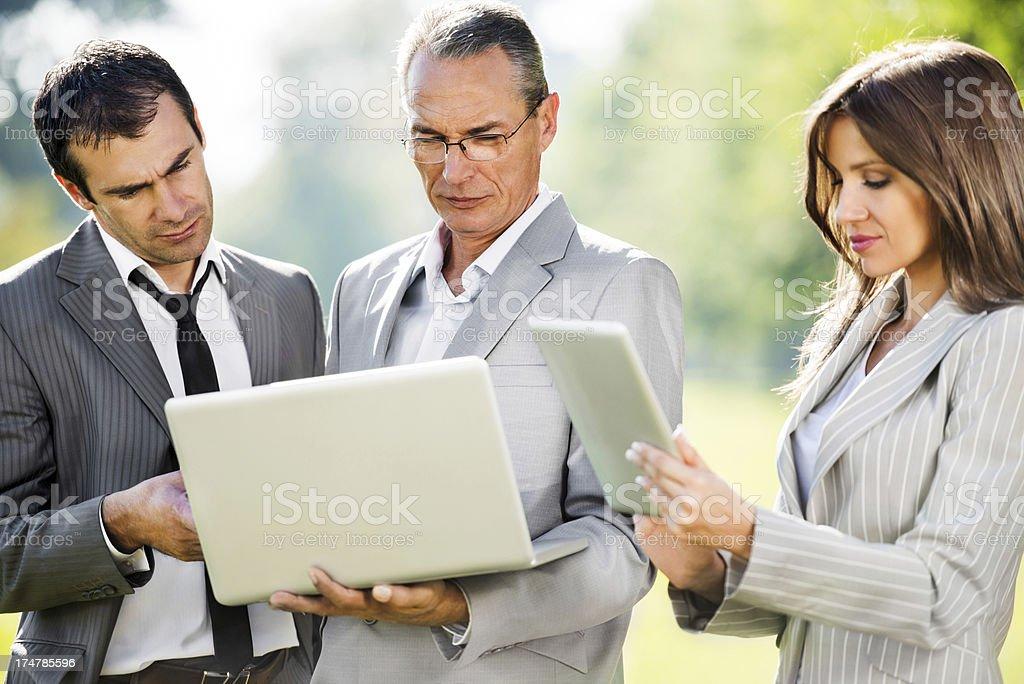 Three businesspeople using wireless technology. royalty-free stock photo