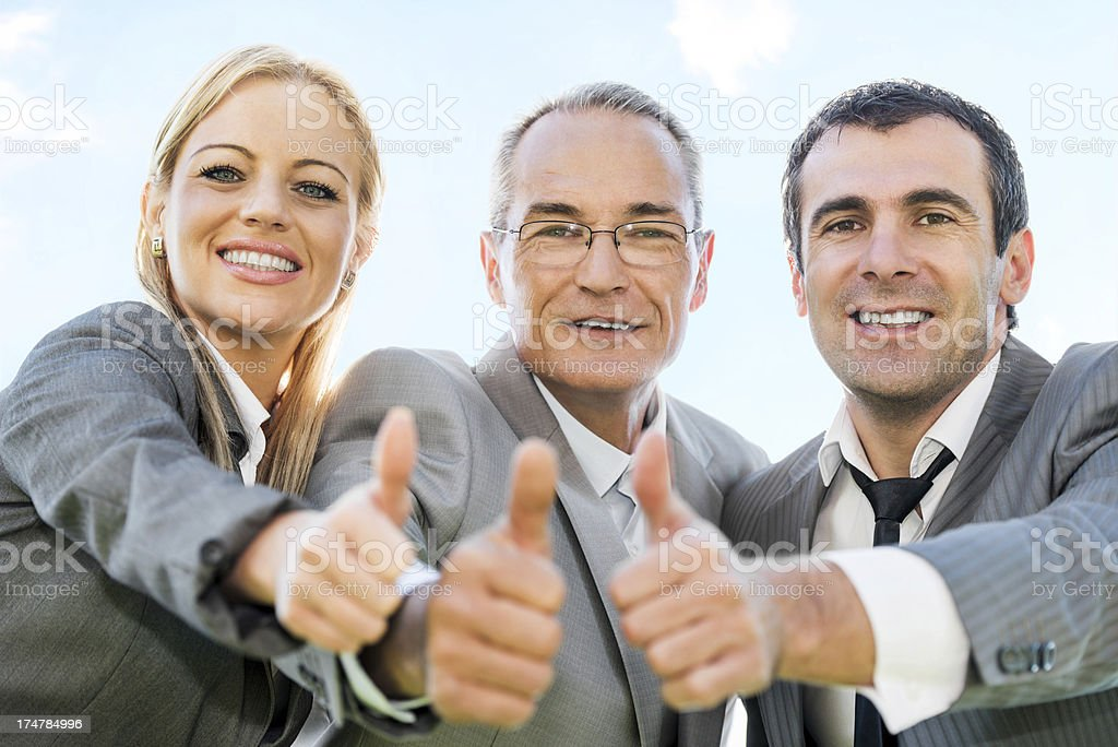 Three businesspeople with thumbs up against the sky. royalty-free stock photo