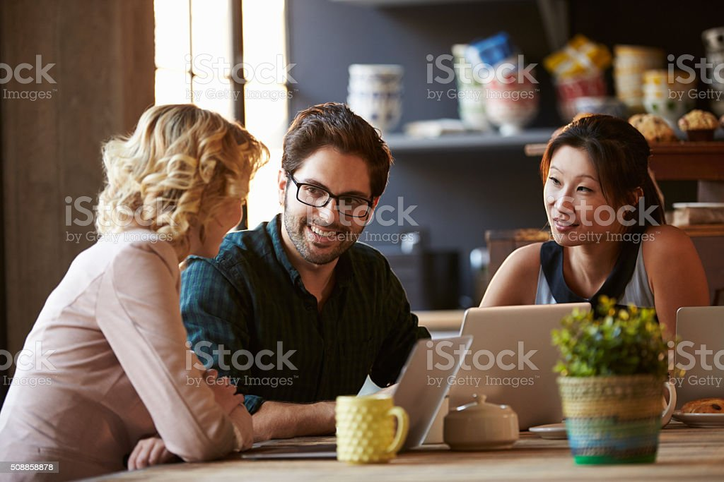Three Businesspeople Working At Laptop In cafe stock photo