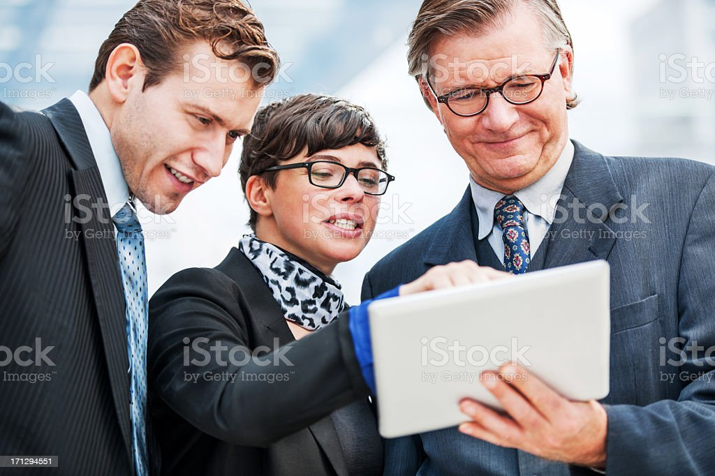 Three businesspeople working on a touchpad. royalty-free stock photo