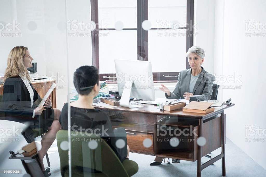 Three businesswomen in meeting behind glass partition stock photo