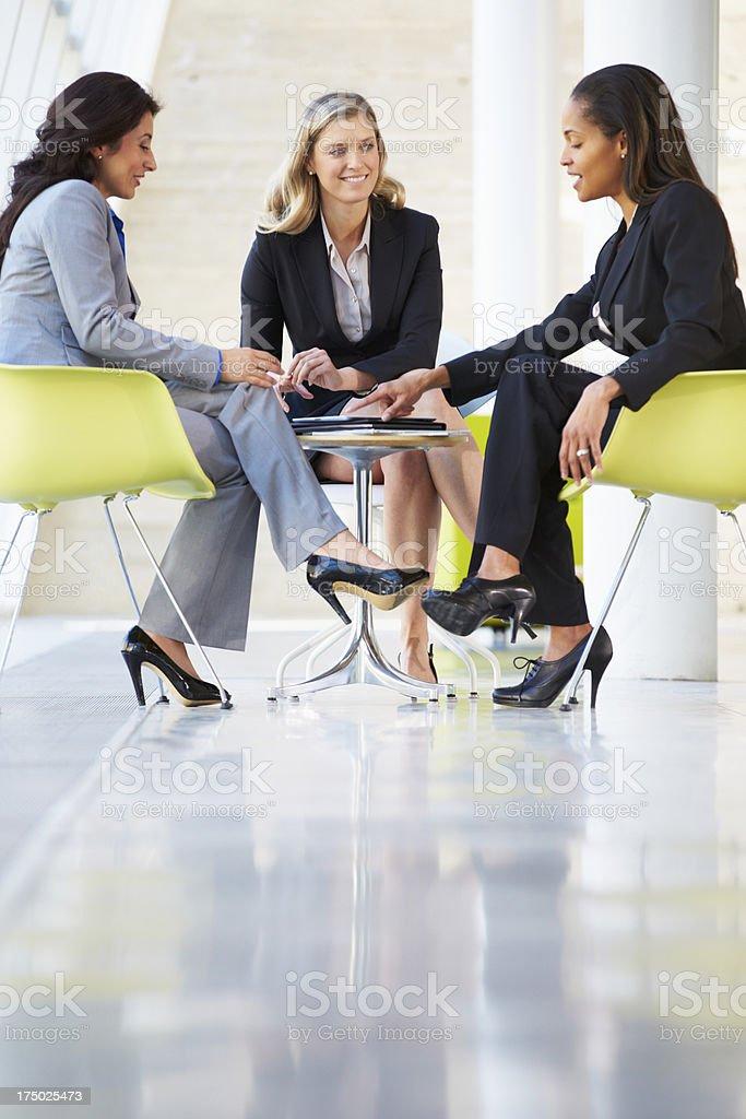 Three Businesswomen Meeting Around Table In Modern Office stock photo