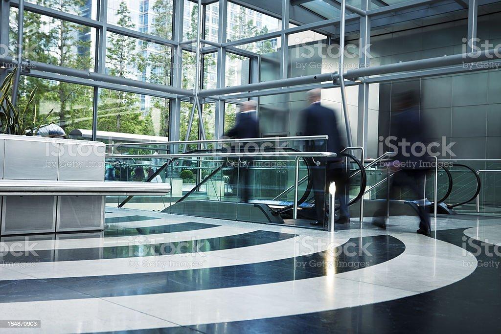 Three Bussinesmen Walking Down Corridor Towards Escalator, Blurred Motion royalty-free stock photo