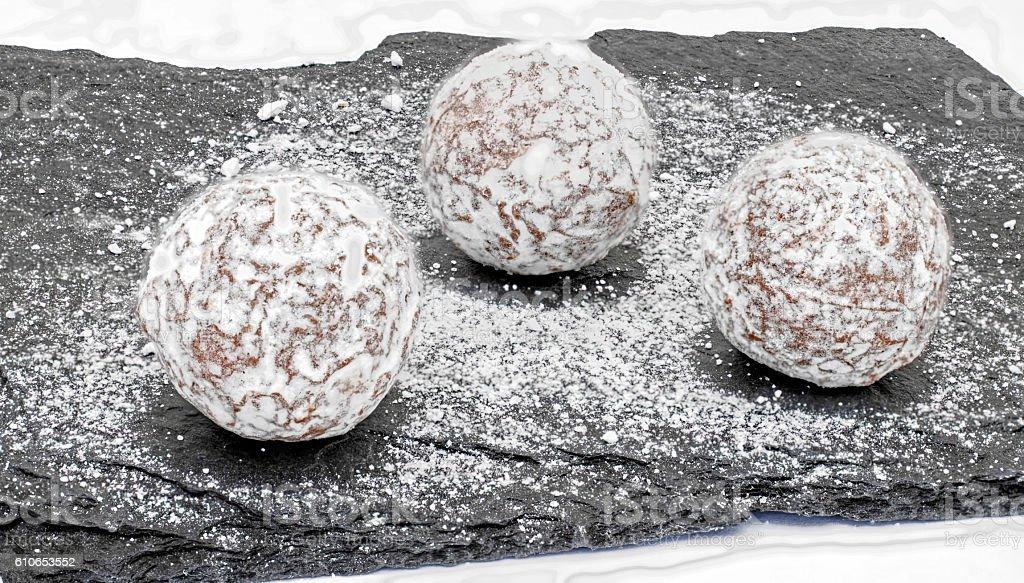 Three butter truffles on a black stone slab stock photo