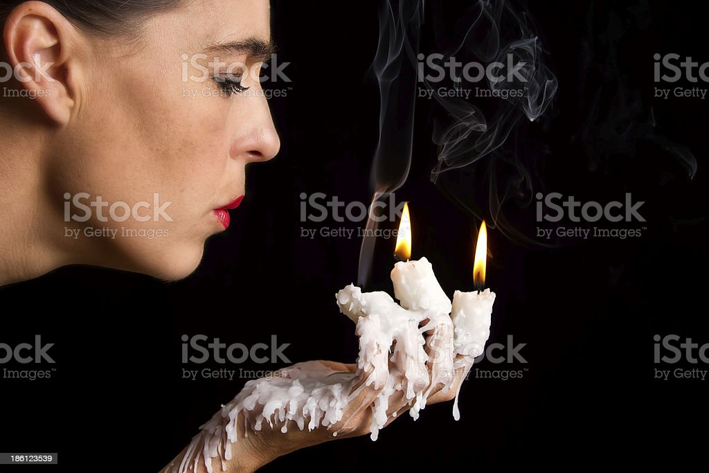 Three candle sticks on fingers buring face blow stock photo