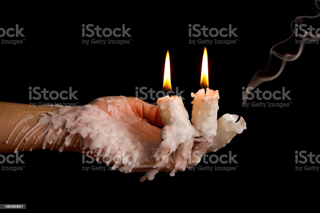 Three candle sticks on fingers buring smoulder stock photo
