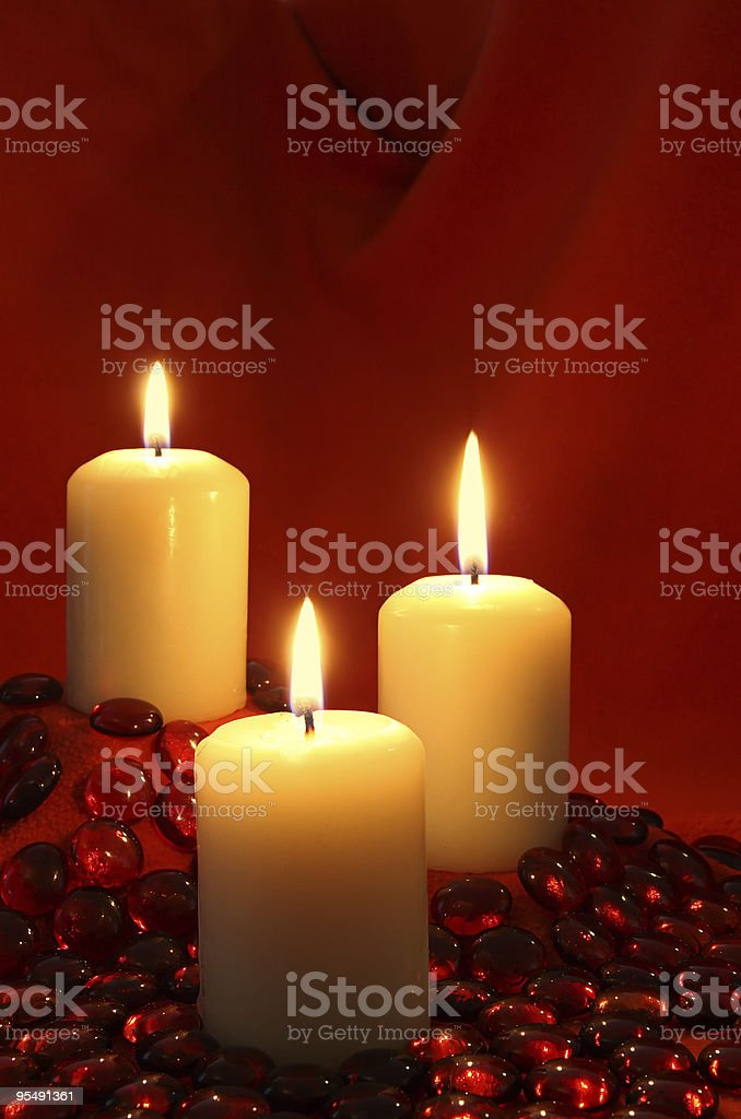 Three candles and red beads on a background ,christmas valentines royalty-free stock photo
